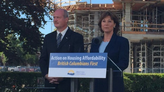 Premier Christy Clark, alongside Finance Minister Mike de Jong, speaks to reporters on July 25, 2016, following the introduction of the foreign homebuyers tax.