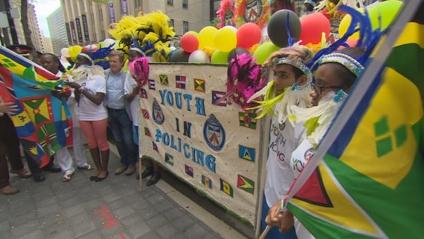 Mayor John Tory and members of Youth in Policing celebrating the launch of the Toronto Police float, which will be part of the Caribbean Festival parade on Saturday.