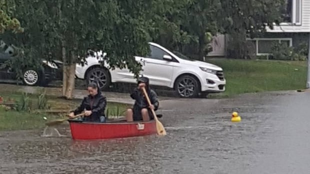 Two people boat down a Fort McMurray, Alta., street as heavy rains caused localized flooding and forced the closure of some roads.