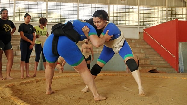 Fernanda Pelegrini, left, and Luciana Watanabe engage in a bout inside the ringed sumo-wrestling circle known as a dohyo in Sao Paulo. Traditionally, women were banned from entering the sacred space, as Japanese originators of the sport believed they brought impurities into the ring.