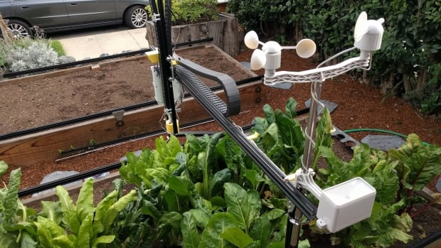 The FarmBot Genesis is a robot that moves around a small garden bed using  tracks on