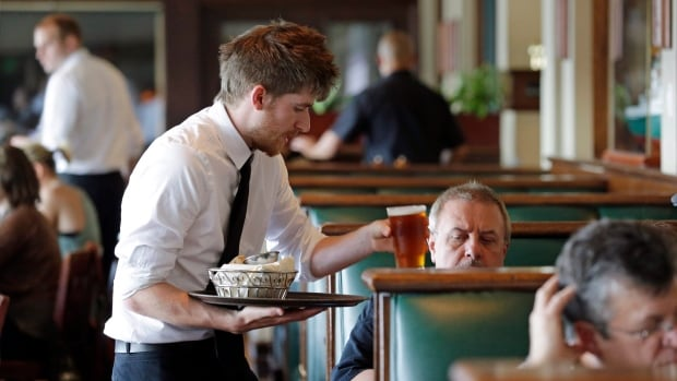 A Seattle waiter serves a customer in this file photo. Mounting a criminal case against a waiter in Sherbrooke, Que., who served fish to an allergic customer could be difficult, a criminal lawyer says.