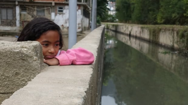At an impoverished neighbourhood not far from the city's new Olympic Park, raw sewage floats down a stream behind dilapidated housing teeming with children playing by the water, oblivious to the health threat.