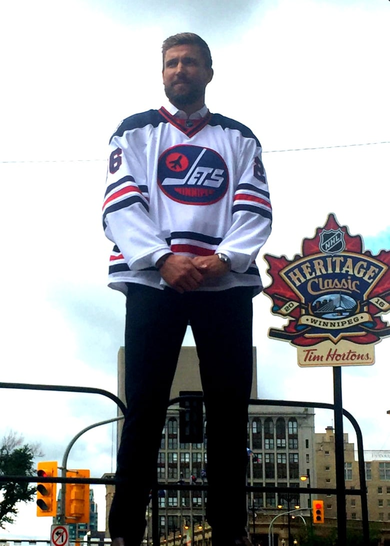 Blake Wheeler of the Winnipeg Jets shows off a classic jersey that the team  will wear at the Heritage Classic. (Brett Purdy CBC) c47587256
