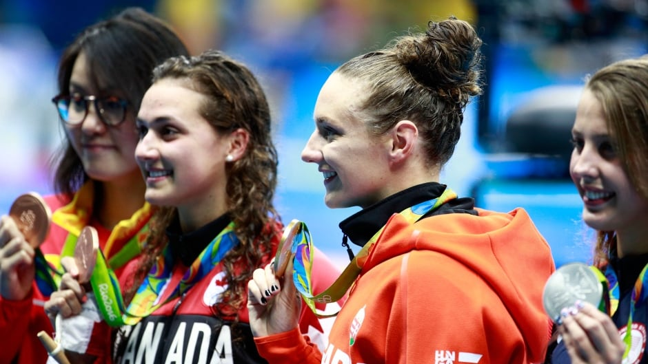 (R-L) Silver medalist Kathleen Baker of the United States, gold medal medallist Katinka Hosszu of Hungary and bronze medalists Kylie Masse of Canada and Yuanhui Fu of China pose on the podium during the medal ceremony for the Women's 100m Backstroke Final on Day 3 of the Rio 2016 Olympic Games.