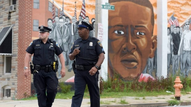 Baltimore police walk near a mural depicting Freddie Gray after prosecutors dropped remaining charges against the three Baltimore police officers on July 27.