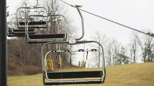 Chairlifts remain idle in the absence of snow at the Glen Eden ski hill in Milton, Ont., on Dec. 22, 2015. A consistent lack of snow due to climate change is a serious threat that has led ski and snowboarding resorts around the world to try to 'weatherproof' their businesses, says Peter Williams, director of Simon Fraser University's Centre for Tourism Policy and Research.
