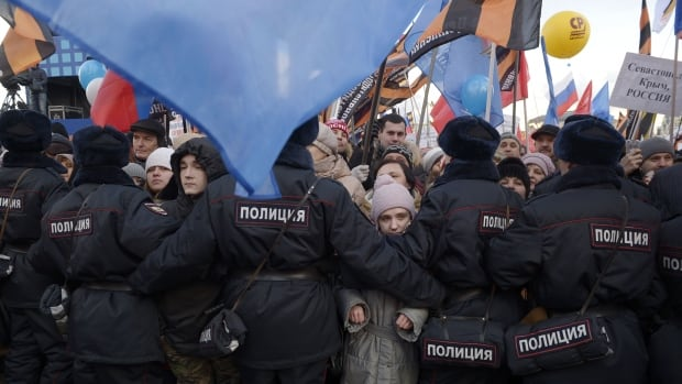 Pro-Kremlin supporters stand behind a police cordon as they attend a rally in Moscow on March 18, 2016, to mark two years since Russian President Vladimir Putin signed off on the annexation of Crimea.
