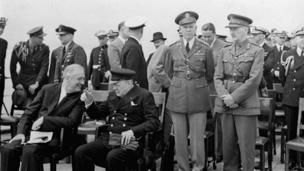 Four months before the U.S. went to war, Franklin Delano Roosevelt and Sir Winston Churchill chat aboard HMS Prince of Wales on August 10, 1941, a rendezvous that gave the world the Atlantic Charter, a prayer book is on Roosevelt's lap. Behind Churchill are General George Marshall, left, chief of staff, and General Sir John G. Dill, chief of Imperial British Staff. To the extreme left behind FDR is Capt. Elliott Roosevelt, his son.
