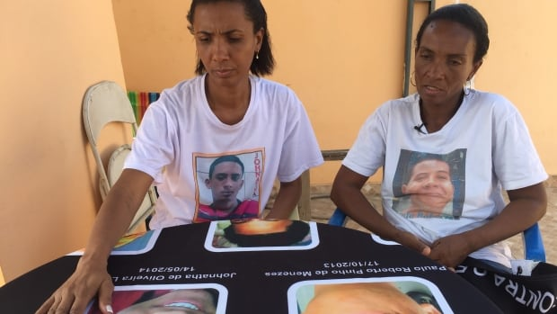Ana Oliveira and Fatima Pinhos look at pictures of their sons, both killed by police.