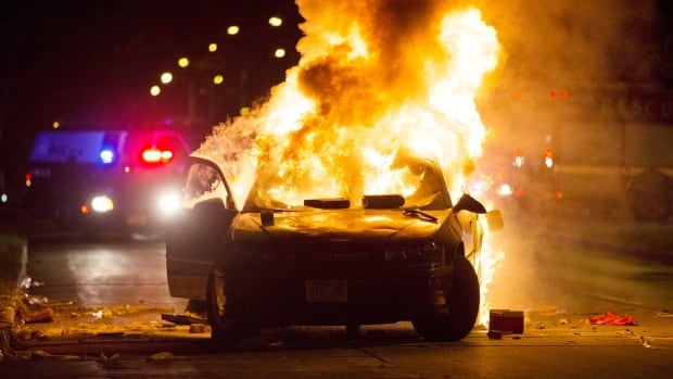 A car burns as a crowd of more than 100 people gathers following the fatal shooting of a man in Milwaukee on Saturday. The gathering occurred in the neighbourhood where a Milwaukee officer shot and killed a man police say was armed.