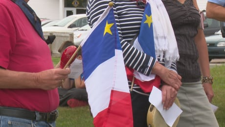 Acadian Day standing with flag
