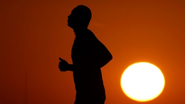 The sun sets behind a jogger on July 21 as the temperature hovers around 38 C in Kansas City, Mo. NASA confirms that July 2016 broke the record for the hottest month since scientists started keeping records in 1880.