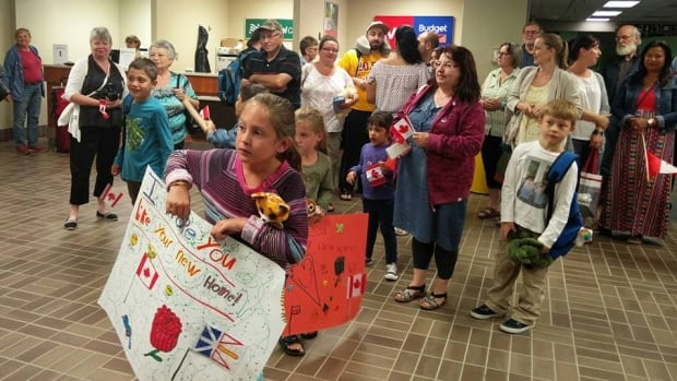Dozens of people await the arrival of a Syrian refugee family in Gander, N.L., in the early morning hours of Aug. 11. Ottawa is now offering private sponsors of  families whose arrival in Canada has been delayed the opportunity to replace them.