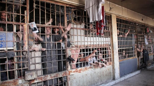 Inmates are seen behind bars in Aleppo's main prison on May 22, 2014. Amnesty International says tens of thousands of people in Syrian prisons have been tortured and nearly 18,000 have died since March 2011.