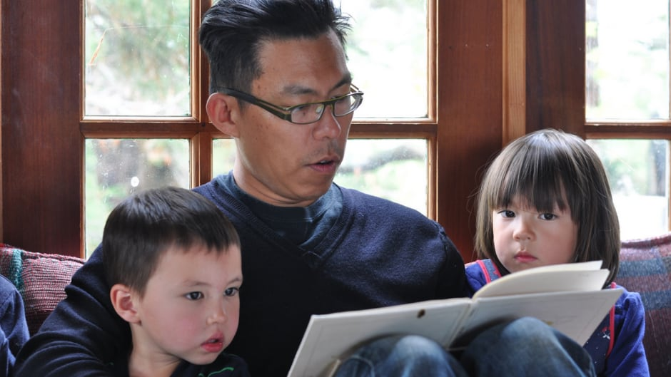 Holman Wang reading to his children, Celia and Felix.