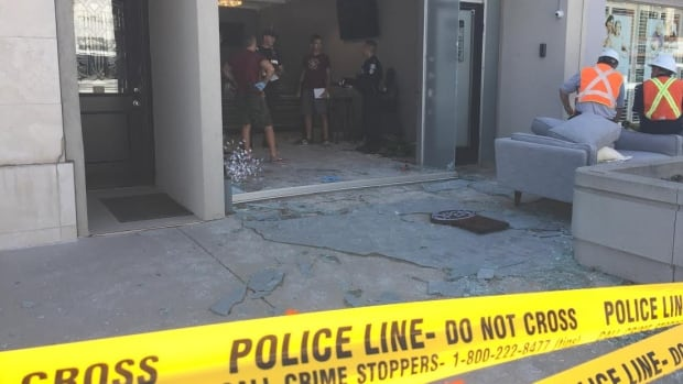 A Toronto police officer talks to Office of the Fire Marshal investigators inside Tweeder Medicinal after an explosion at the marijuana dispensary injured a man on Friday.