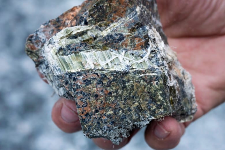 A former asbestos mine worker holds a chunk of the mineral fibre.