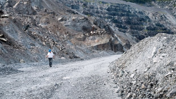 A former mine worker in August walks along the banks of the open pit of the now closed Jeffrey mine in Asbestos, Que.