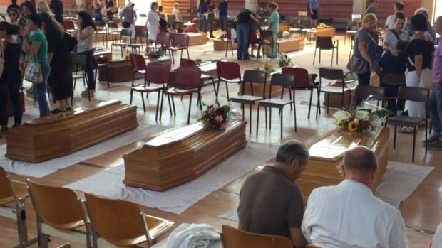 People gather at coffins in the gymnasium on Friday.