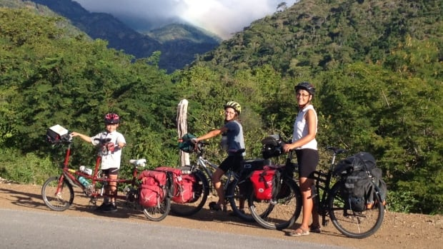 From left to right, 10-year-old Jasper Hefferman-Wilker, 13-year-old Anna Sierra Hefferman-Wilker, and their mother Kathleen Wilker pose with their bicycles on a mountain road in Cuba. The family recently returned from a year-long bike trip that spanned seven countries.