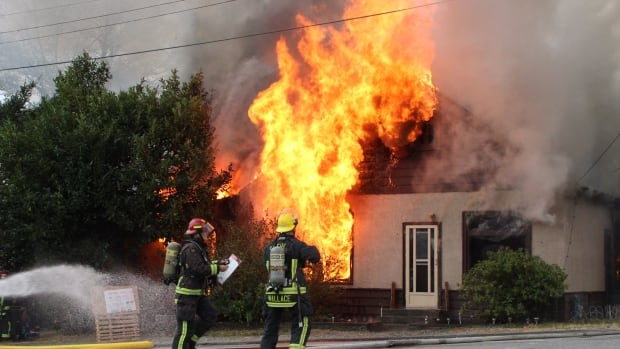 Firefighters battle to stop a fire in Surrey, B.C. at a home neighbours say was slated to be demolished.