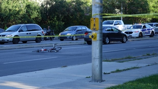 A bicycle and car remain inside a taped-off area of the Vanier Parkway after a collision involving a cyclist early Monday morning.