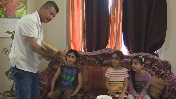 Najim Altememy shows off honey combs to his three young daughters.