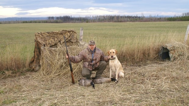 Tony Manuge, pictured here earlier with Charlie, his golden labrador. Charlie suffered deep cuts and scratches after he charged a black bear Saturday.