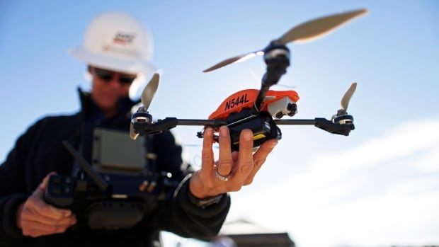 San Diego Gas & Electric drone operator Teena Deering holds a drone as it prepares for takeoff. Unmanned aerial vehicles are used to inspect the company's power lines in remote areas. New U.S. rules took effect this week, allowing companies to fly drones for commercial purposes without needing a manned-aircraft pilot's licence.