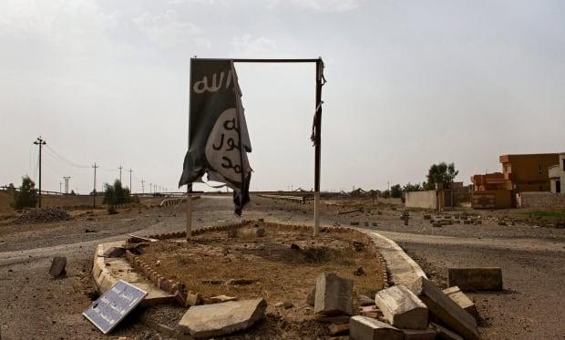 Mideast Iraq ISIS banner Qayara oil wells