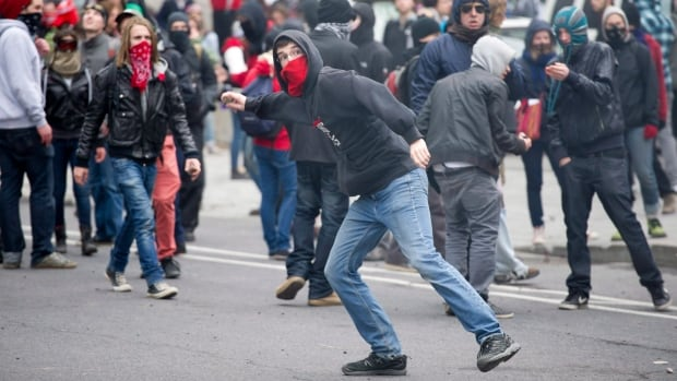 A demonstrator throws a rock towards the police line during a student demonstration outside the Montreal convention centre.