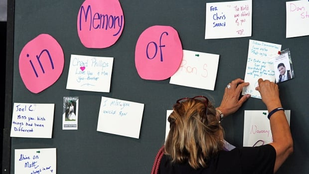 A woman pins a message to a memory board erected outside Hamilton City Hall as part of International Overdose Awareness Day, a global event held on Aug. 31 that aims to raise awareness of overdose, reduce stigma, and to prevent overdose deaths.