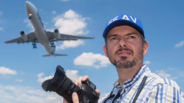 Plane spotting enthuasist Jean-Charles Hubert looks on as an Air Transat Airbus A330 lands at Montreal's Trudeau Airport, Sunday, July 31, 2016.