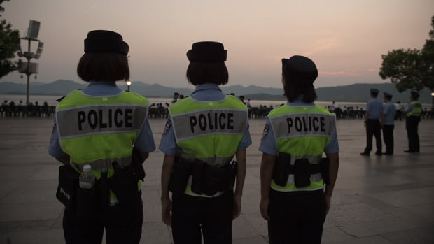 Police officers secure an area in Hangzhou, China. Factories have been closed to ensure blue skies, potential troublemakers detained, and a quarter of the residents have left after being offered 'vacation vouchers,' all to make sure the city will look its best for the G20 summit.