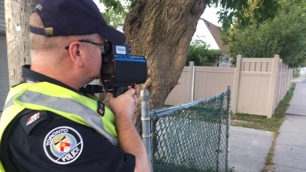 A Toronto police officer trains his radar gun on the road outside Second Street Junior Middle School on the first day of the force's back-to-school safety blitz.