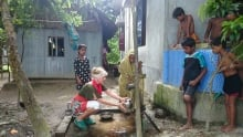Judit collecting well water with villager