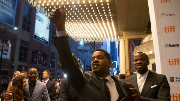 The Birth of a Nation director, writer, producer and star Nate Parker, centre, gestures to the crowd as he arrives for his film's first public screening at the 2016 Toronto International Film Festival in Toronto on Friday. Can the lauded slave rebellion drama escape a furor sparked by the filmmaker's past?
