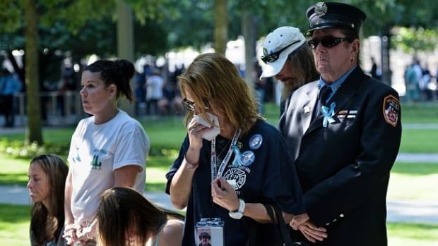 People observe a moment of silence during the memorial service at the National 9/11 Memorial in New York