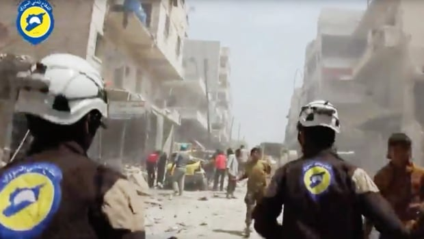 White Helmets volunteers run after airstrikes and shelling hit Aleppo, Syria in April 2016. The founder of the group, Raed Saleh, and a young Syrian rescue worker who shot scenes for the Oscar-nominated doc are unable to attend the Feb. 26 Oscars ceremony due to Trump's executive order.