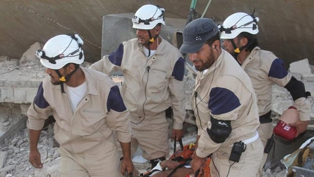A group of White Helmets volunteers in northern Syria carry one of their comrades during a training session, in Idlib province, northern Syria.