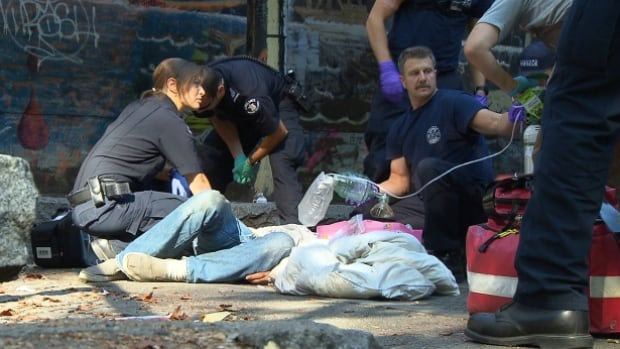Paramedics and firefighters work to revive an overdose patient with repeated doses of naloxone, the antidote to opiods such as fentanyl.