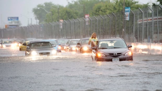A woman gets out of her car to check it in floodwater in Toronto back in 2013.