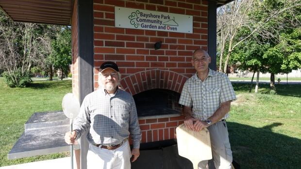 Tom Marcantonio, left, and Mete Pamir stand in front of their beloved community oven ahead of the community's Harvest Fair Saturday, Sept. 17, 2016.