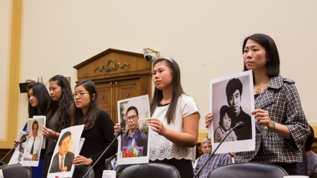 Ti-Anna Wang (centre, in black) says Prime Minister Justin Trudeau should 'unequivocally demand' the release of her father, Wang Bingzhan.