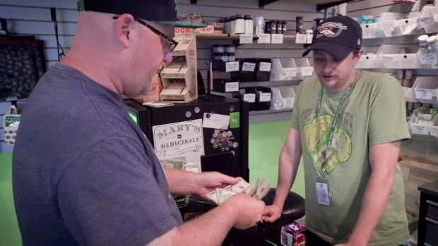 A customer pays cash for marijuana at the Dank dispensary in Denver.