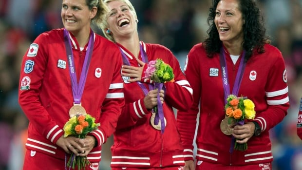 Canada women's soccer players Christine Sinclair,  Sophie Schmidt, and Melissa Tancredi are shown in this August 2012 file photo. The three teammates, along with Rhian Wilkenson, were among the latest athletes targeted by Russian hackers.