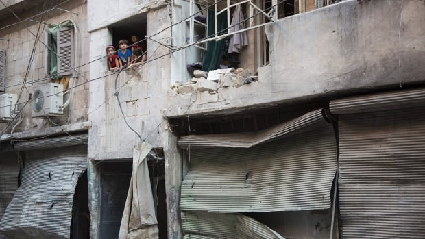 Syrian children look at the damage following an airstrike in Aleppo's rebel-controlled neighbourhood of Karm al-Jabal on Sunday. On Monday, an aid convoy was hit in a rural western area of Aleppo province.