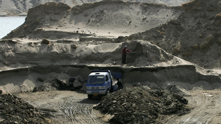 Chinese laborers extract sand from dirt along the river bank March 19, 2006 on the outskirts of Beijing, China. The sand that they mine will be used to build new houses.