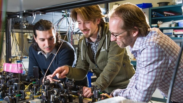From left, postdoctoral fellows Daniel Oblak, Erhan Saglamyurek and physics professor Wolfgang Tittel, look over lab equipment. Their team recently published a paper on quantum computing advances.